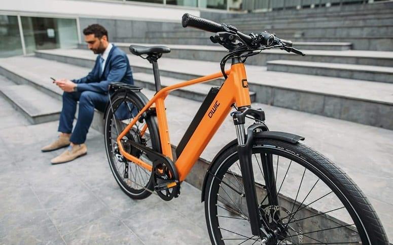 Businessman Sitting Next To Orange Ebike