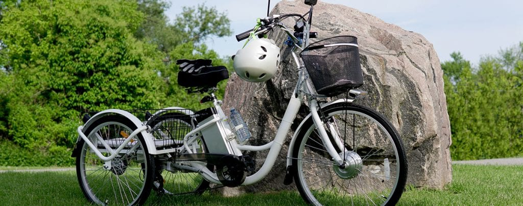 electric trike against a rock with safety equipment