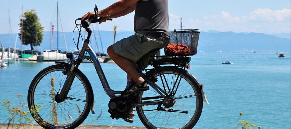 man riding best electric beach cruiser by the ocean